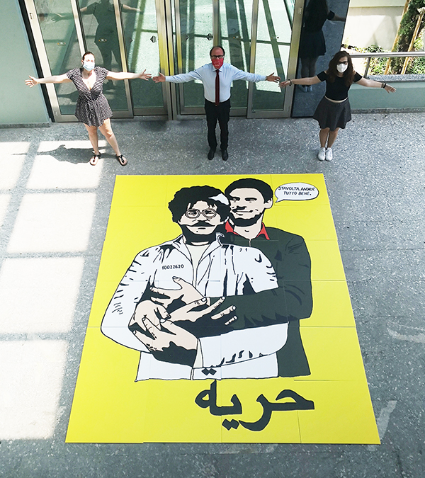 Il pannello nella sede di UniTe con l'immagine della street artist LAIKA che ritrae Giulio Regeni che abbraccia Patrick Zaky, con la frase «Questa volta andrà tutto bene!»